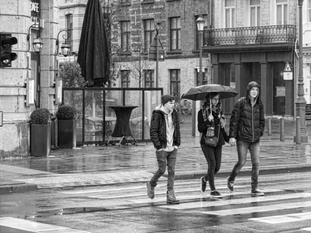 3 college students walking in  the rain. One holding a best college umbrella!