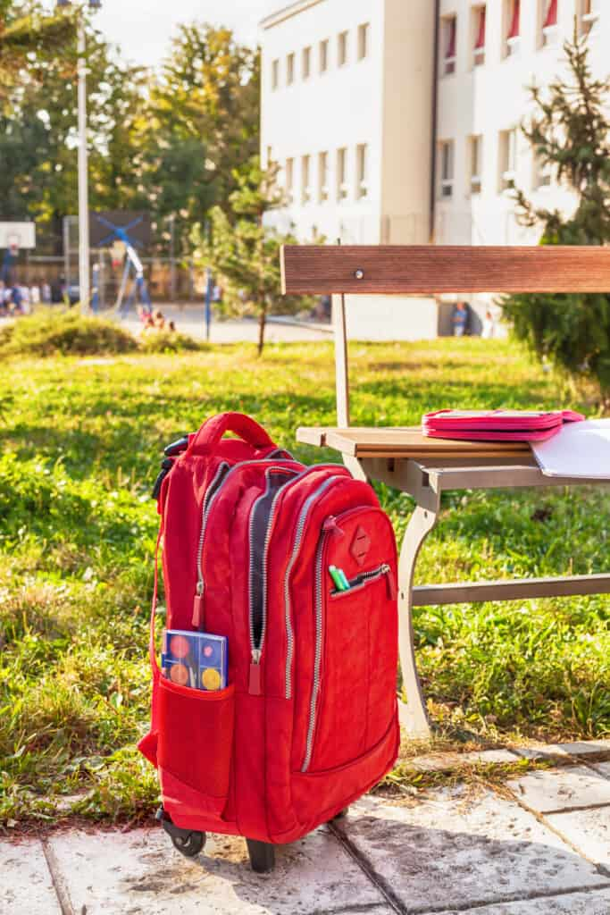 Red rolling backpack for students by a bench