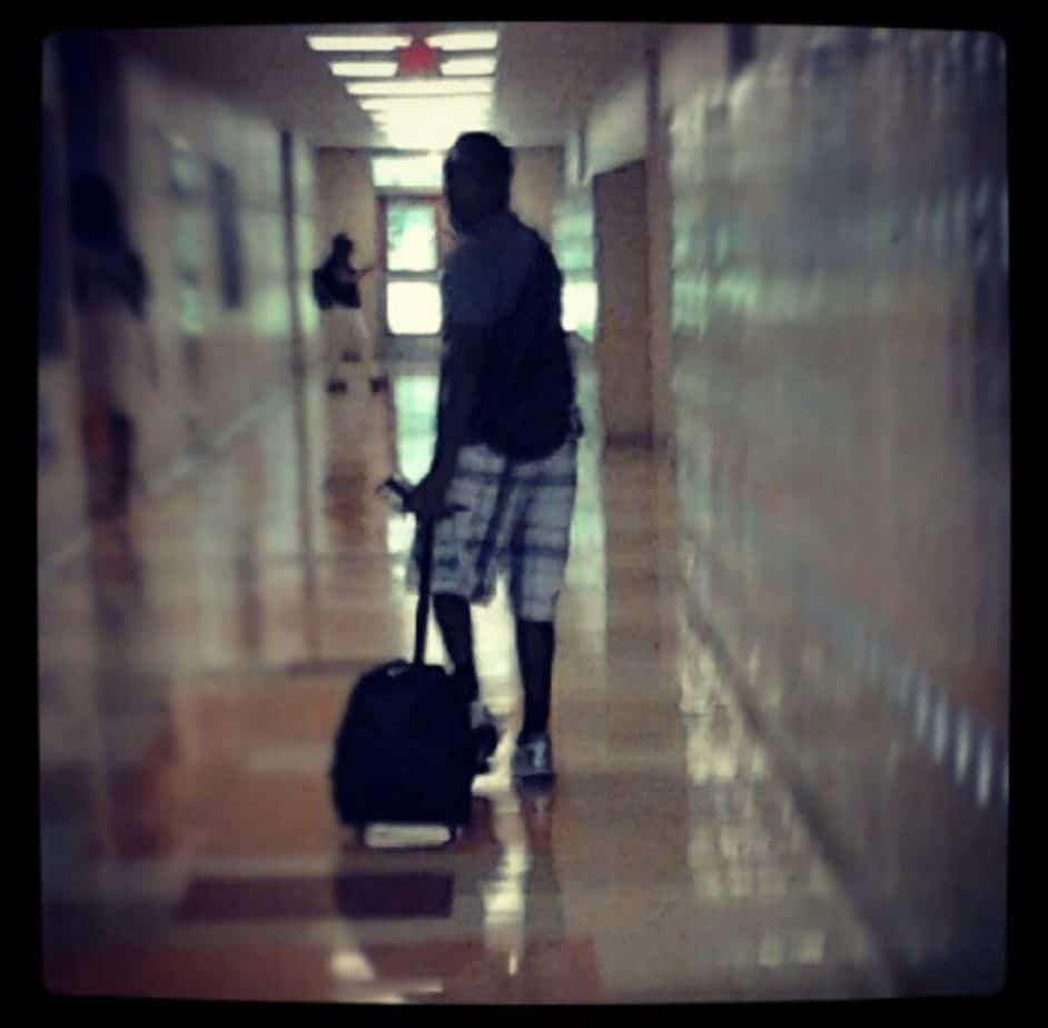 A student wheeling their rolling bookbag